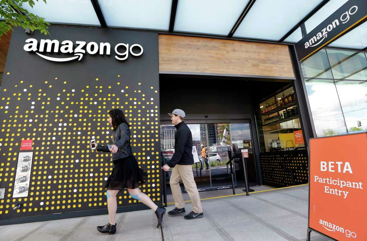 FILE - In this Thursday, April 27, 2017, file photo, people walk past an Amazon Go store, currently open only to Amazon employees, in Seattle. Amazon Go shops are convenience stores that don't use cashiers or checkout lines, but use a tracking system that of sensors, algorithms, and cameras to determine what a customer has bought. Amazon says the company has no plans to use such sensors to automate the cashier jobs at Whole Foods, which Amazon is acquiring. Still, itÂ?'s the kind of technology that could help cut costs down the road, and that others may look to as well. (AP Photo/Elaine Thompson, File)