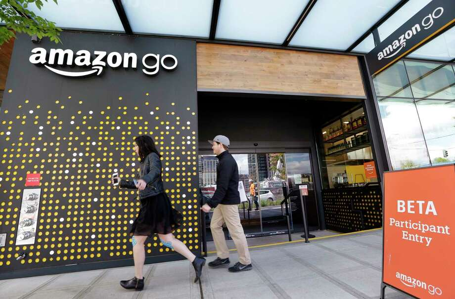 FILE - In this Thursday, April 27, 2017, file photo, people walk past an Amazon Go store, currently open only to Amazon employees, in Seattle. Amazon Go shops are convenience stores that don't use cashiers or checkout lines, but use a tracking system that of sensors, algorithms, and cameras to determine what a customer has bought. Amazon says the company has no plans to use such sensors to automate the cashier jobs at Whole Foods, which Amazon is acquiring. Still, it's the kind of technology that could help cut costs down the road, and that others may look to as well. (AP Photo/Elaine Thompson, File) Photo: Elaine Thompson, STF / Copyright 2017 The Associated Press. All rights reserved.