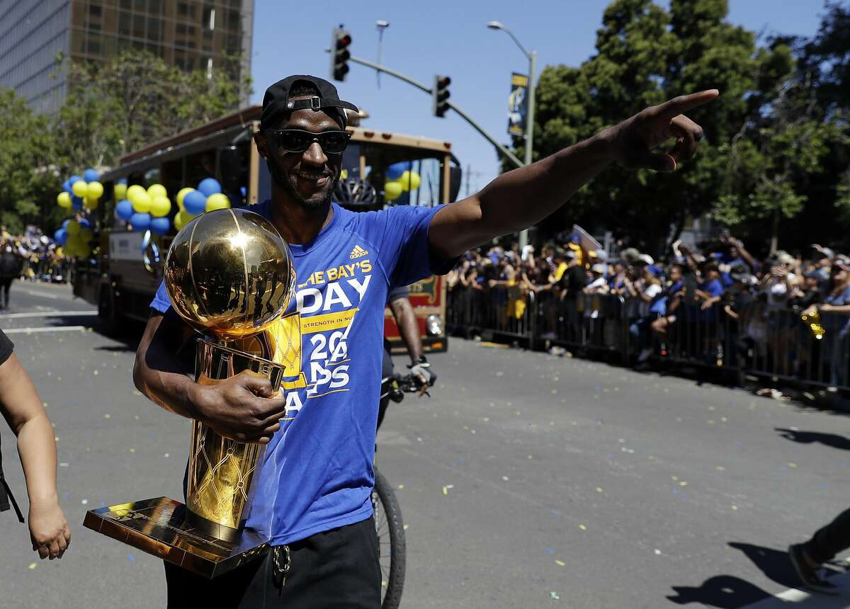 Golden State Warriors' Ian Clark holds the Larry O'Brien trophy during a parade and rally after the Warriors won the NBA basketball championship Thursday, June 15, 2017, in Oakland, Calif. (AP Photo/Marcio Jose Sanchez)