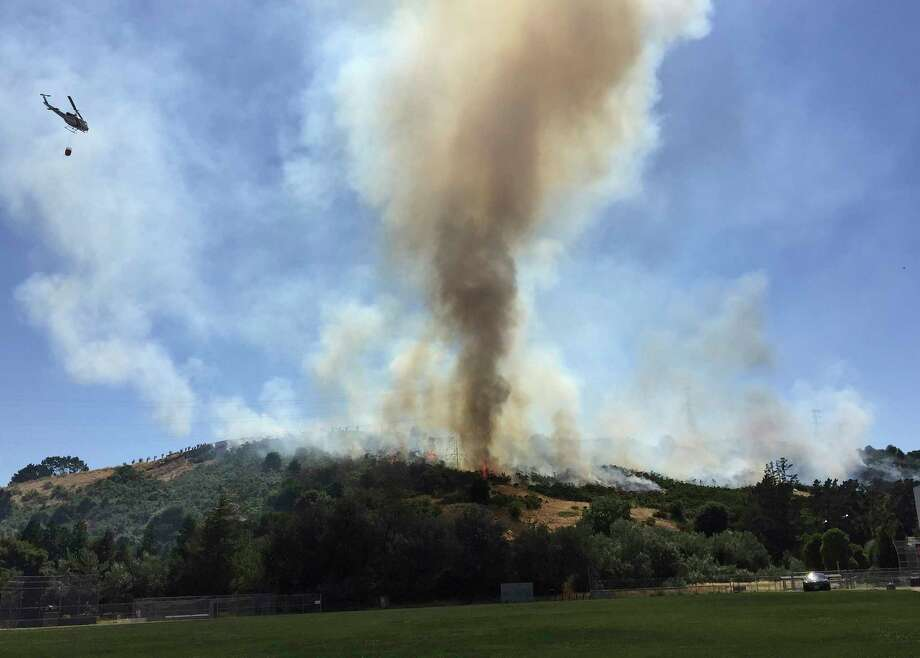 In this photo provided by Jocelyn Gecker, a helicopter flies over Moraga, Calif., as part of efforts Monday, June 19, 2017, to put out a grass fire that had burned through several acres behind Campolindo High School and was threatening homes. Contra Costa County fire officials say the blaze started Monday afternoon behind the high school. (Harrison Fuller via AP) Photo: Harrison Fuller, AP / Jocelyn Gecker