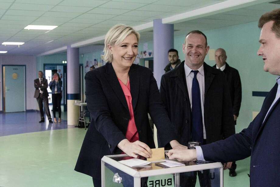French presidential candidate Marine Le Pen casts her vote in a ballot box at a polling station during the second round of the French presidential election in Henin Beaumont France