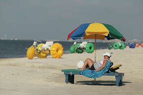 BILOXI, MS - JULY 04: Sheila Tribe sits on the near-empty beach as businesses hope that beachgoers appear as the day gets under way and are not shying away because of the Deepwater Horizon oil spill in the Gulf of Mexico on July 4, 2010 in Biloxi, Mississippi. Tribe said she would normally spend 4th of July on the beach in Grand Isle, Louisiana which is near her home but because of the beach closure she couldn't. The oil spill may have a huge negative economic impact on gulf coast businesses during what should be a busy 4th of July. Millions of gallons of oil have spilled into the Gulf since the April 20 explosion on the drilling platform. (Photo by Joe Raedle/Getty Images)