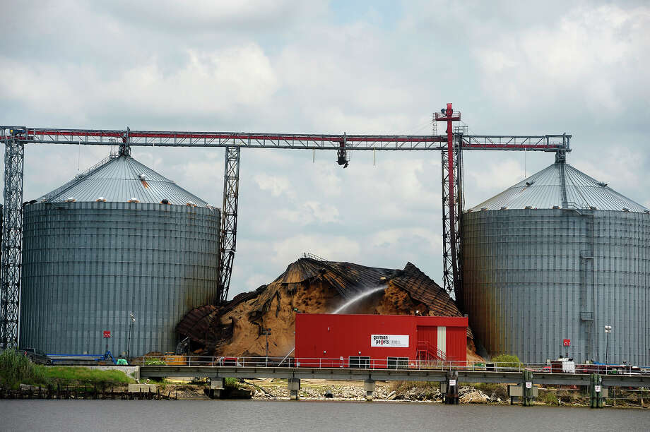 Water is sprayed on a pile of wood pellets that have been smoldering since February in Port Arthur on Monday. The silo collapsed two weeks ago, and now an increase in temperature has been noticed in an adjacent silo.  Photo taken Monday 6/19/17 Ryan Pelham/The Enterprise Photo: Ryan Pelham / ©2017 The Beaumont Enterprise/Ryan Pelham