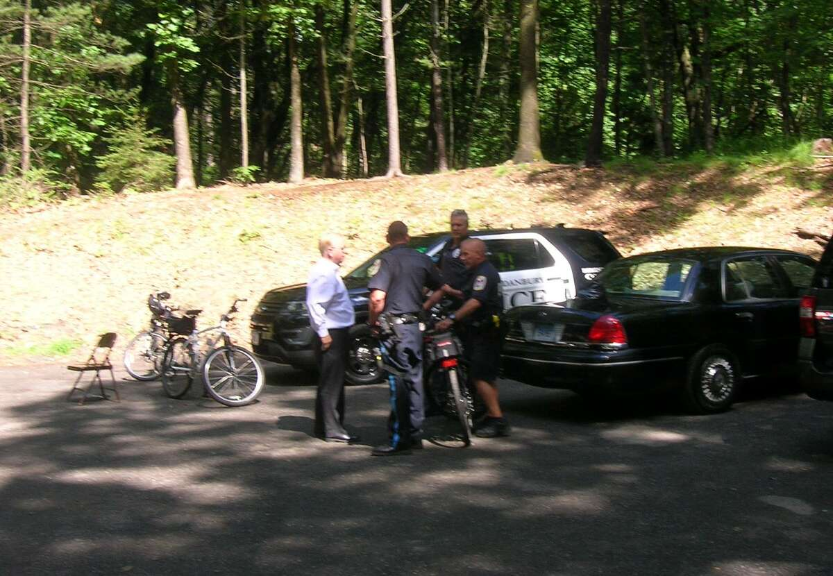 Danbury Mayor Mark Boughton checks in with the police department's bicycle unit as emergency officials continue the search for a lost mountain biker at Farrington Woods on the city's west side Tuesday.