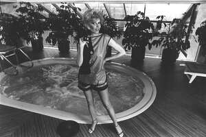 04/1983 - After her Jacuzzi, Dallas Hill slips on Michaele Vollbracht's polished cotton coverup and shorts, from the resort collection at Saks Fifth Avenue.