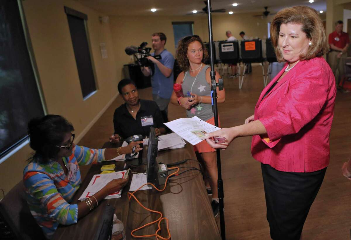 Karen Handel, Republican candidate for Congress, checks in for her voter card Tuesday, June 20, 2017, at the 6th District Special Election at St Mary's Orthodox Church in Roswell, Ga. The matchup of Republican Handell and Democrat Jon Ossoff has become a proxy for the national political atmosphere and a test of GOP strength early in Donald Trump's presidency. (Bob Andres/Atlanta Journal-Constitution via AP)
