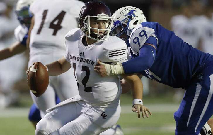 Katy Cinco Ranch quarterback James Klingler (12) gets sacked by Katy Taylor's Max Wright (99) during the first half oat Rhodes Stadium on Oct. 6, 2016 in Katy.