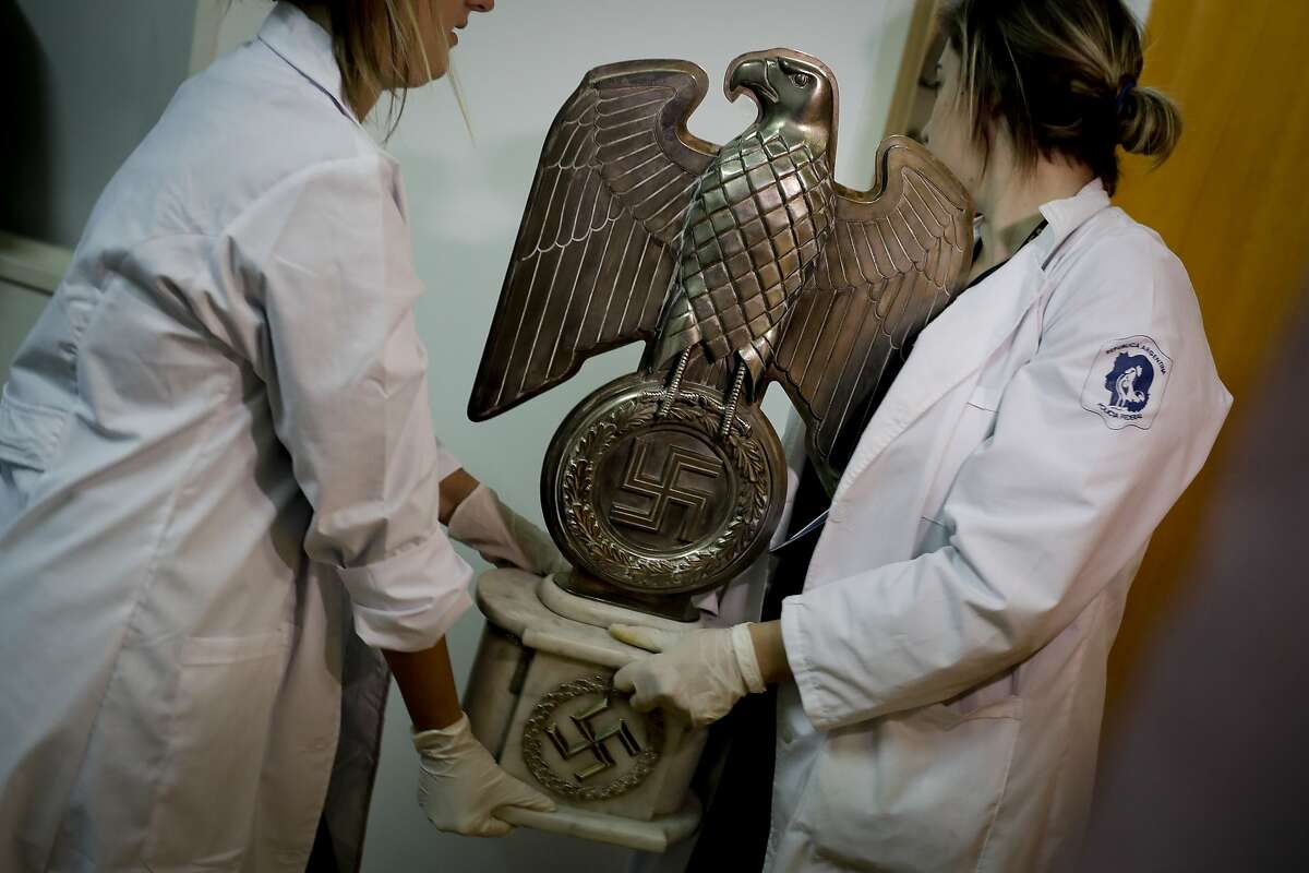 Members of the federal police carry a Nazi statue at the Interpol headquarters in Buenos Aires, Argentina, Friday, June 16, 2017. In a hidden room in a house near Argentina's capital, police discovered on June 8th the biggest collection of Nazi artifacts in the country's history. Authorities say they suspect they are originals that belonged to high-ranking Nazis in Germany during World War II. (AP Photo/Natacha Pisarenko)
