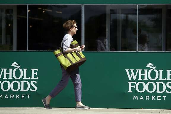 A shopper leaves a Whole Foods Market in Northbrook, Ill., Saturday, June 17, 2017. Amazon is buying Whole Foods in a deal valued at about $13.7 billion, a strong move to expand its growing reach into groceries. (AP Photo/Nam Y. Huh)