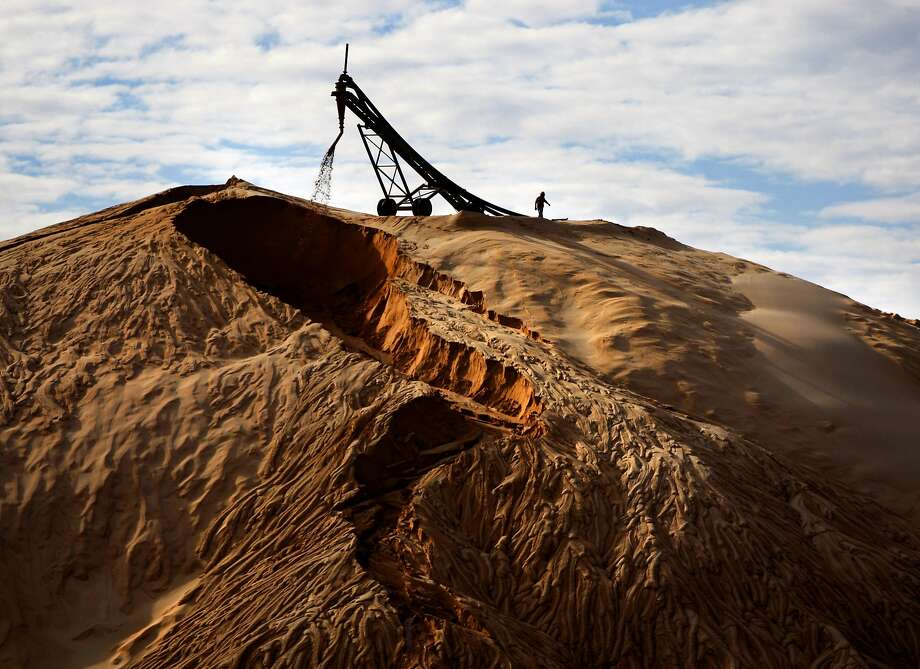 A man walks on the top of a sand pile at the Unimin strip mine facility Thursday Nov. 6, 2014 east of Brady near the community of Voca. The sand strip mines extract silica sand that is used in fracking in the Eagle Ford shale, among other places. Photo: William Luther, San Antonio Express-News