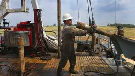 An oil worker unloads pipe at a drilling site. Texas' oil and gas industry has seen steady gains over the last eight months, but while the state is producing more oil and making more money, employment gains have been uneven.