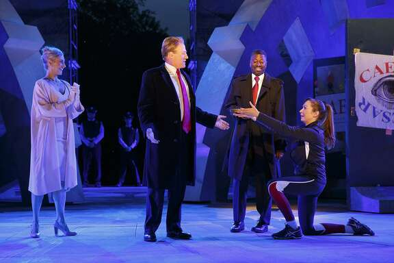 """FILE - In this May 21, 2017, file photo provided by The Public Theater, Tina Benko, left, portrays Melania Trump in the role of Caesar's wife, Calpurnia, and Gregg Henry, center left, portrays President Donald Trump in the role of Julius Caesar during a dress rehearsal of The Public Theater's Free Shakespeare in the Park production of Julius Caesar in New York. Teagle F. Bougere, center right, plays as Casca, and Elizabeth Marvel, right, as Marc Anthony. Shakespeare & Company in Lenox, Mass., said vicious emails it's gotten from people angry about a production of """"Julius Caesar"""" in which a Donald Trump-like character gets assassinated are misdirected since it had nothing to do with the play in New York. The theater is using the mistake as a teachable moment. (Joan Marcus/The Public Theater via AP, File)"""
