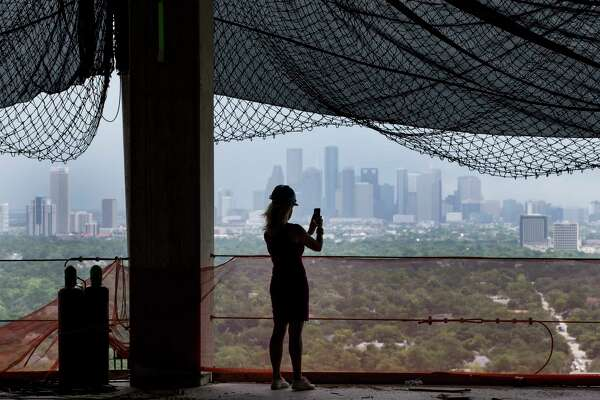 DeeAnn Thigpen takes a photo from the 26th floor, with a view of downtown, at Arabella, a 33-story residential tower under construction just inside the West Loop off San Felipe. Many potential residents also like a view of the Uptown area.