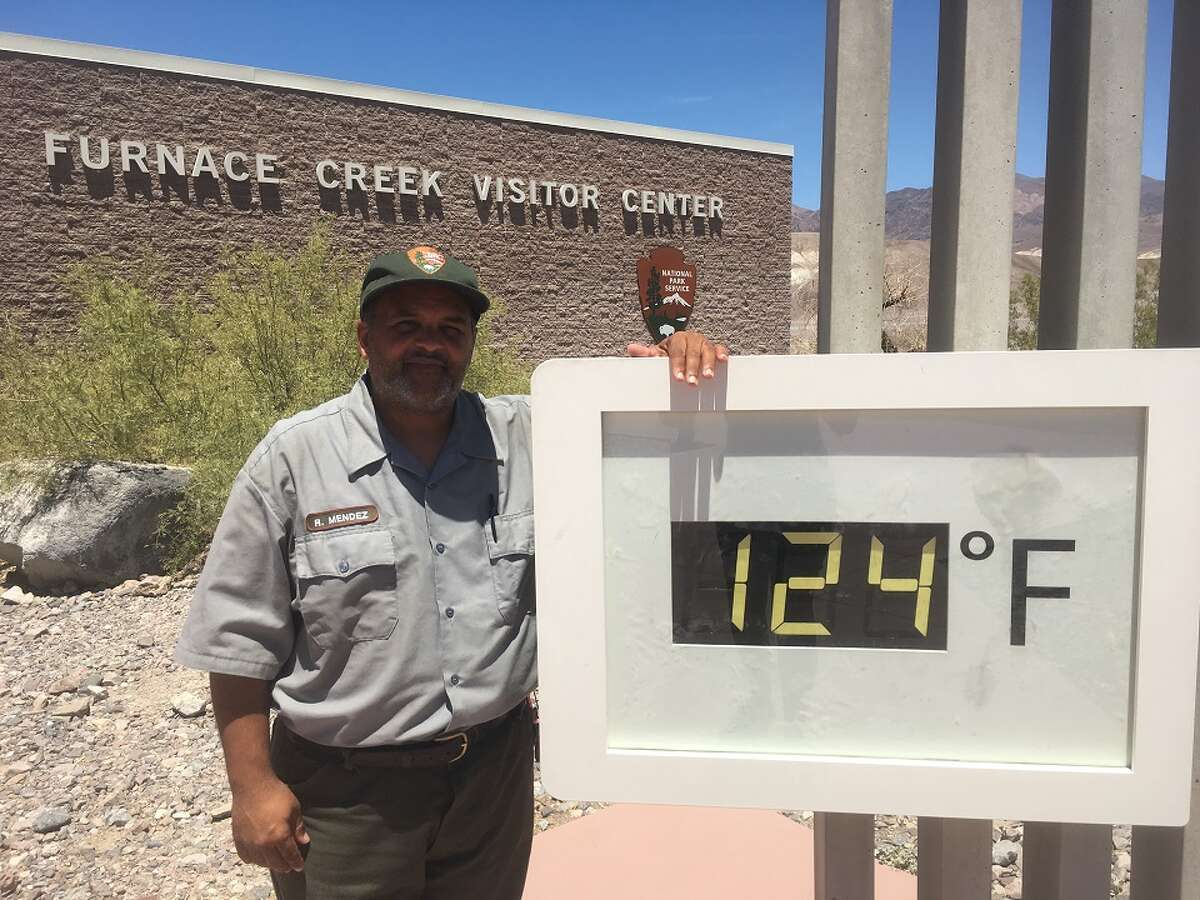 Death Valley National Park Ranger Roberto Mendez stands next to the temperature display outside Furnace Creek Visitor Center.