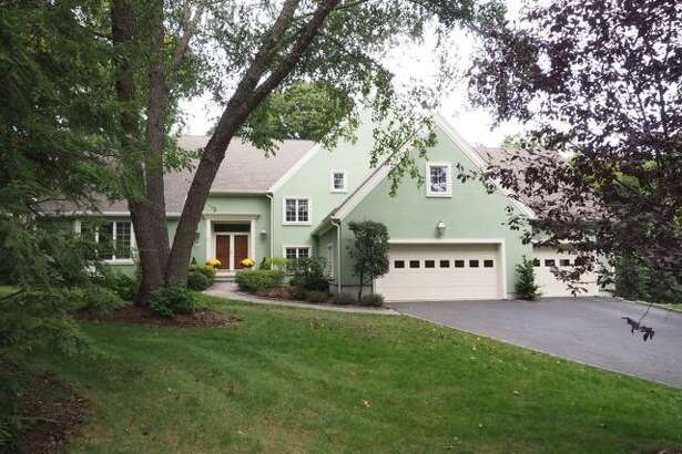 The pale green stucco colonial house at 14 Bates Farm Road sits on a half-acre level and sloping property at the end of a private cul-de-sac in a quiet setting close to town, train and municipal parks.