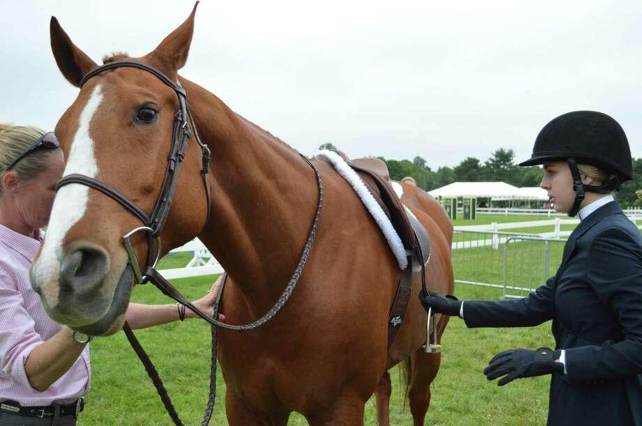 Annie Salvi, 14, of Darien, gets ready to mount her steed at the Ox Ridge Hunt Club's June Horse Show, Saturday, June 17, 2017, in Darien, Conn. Photo: Jarret Liotta / For Hearst Connecticut Media / Darien News Freelance