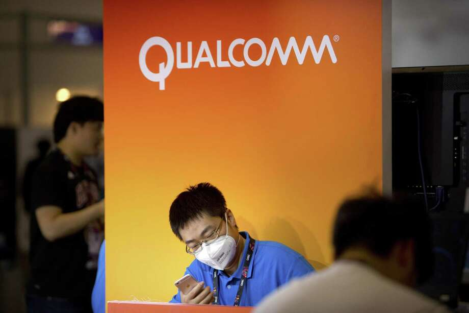 An employee wearing a face mask checks his cellphone at a display booth for Qualcomm at the Global Mobile Internet Conference in Beijing. Apple is intensifying its legal battle with Qualcomm over the technology in iPhones and iPads as Apple seeks to void some of the chip makers patent claims and licensing agreements. Qualcomm has disputed Apples claims that Qualcomm is overcharging for patent-related license fees on iPhone and iPad sales. Photo: Associated Press File Photo / Copyright 2017 The Associated Press. All rights reserved.