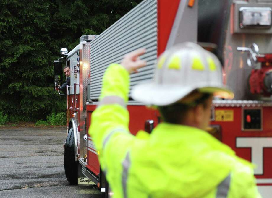 A fire truck is guided backward to unload water during a firefighters' drill in northern Stamford. Photo: Tyler Sizemore / Hearst Connecticut Media / Greenwich Time