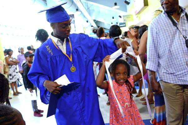 Graduate Darnell Ellis lets his cousin Danielle Fearson, 5, wear his honor society sash after Warren Harding High School's Ninety First Annual Commencement held at the Webster Bank Arena in Bridgeport, Conn., on Tuesday June 20, 2017.