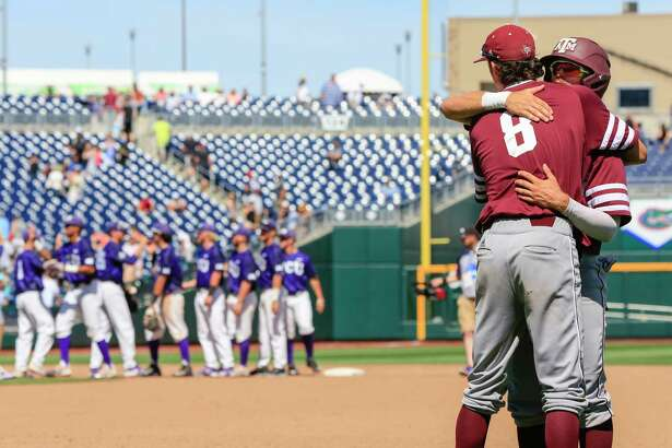 Texas A&M's Braden Shewmake (8) and Blake Kopetsky, right, hug as TCU players celebrate, left, following an NCAA College World Series baseball elimination game in Omaha, Neb., Tuesday, June 20, 2017. TCU won 4-1, eliminating Texas A&M from the tournament. (AP Photo/Nati Harnik)
