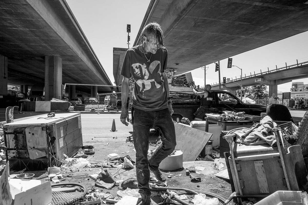 Andrew Haid checks for scrap metal to fill the truck outside his camp at 5th and Market Street on Friday, June 9, 2017, in Oakland, Calif.