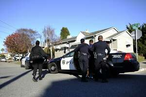 Richmond Police Officers put a suspect into a cruiser near a home where a burglary-in-progress was reported in Richmond, CA, on Tuesday, January 6, 2015.   The city of Richmond has seen a precipitous drop in crime in the last few years and tallied only 11 homicides in 2014.