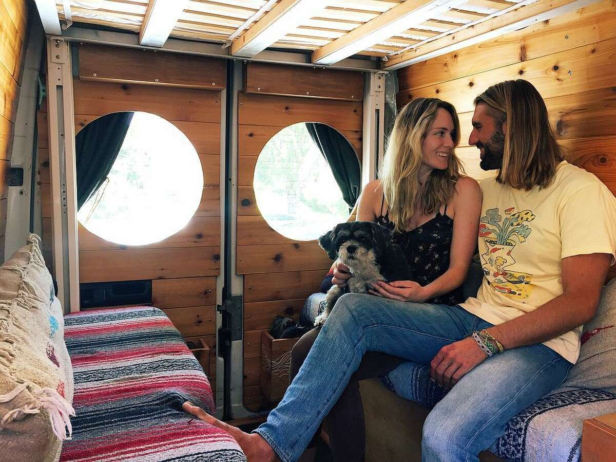 Juliana Linder and Richmond Hollen sit in their renovated Freightliner Sprinter van, along with their dog, Roscoe. Scroll through the slideshow to view more photos of their travels and read more on their experiences of living in a van.
