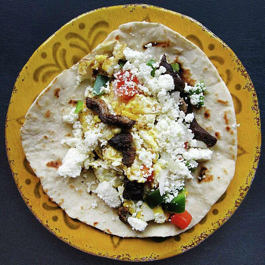 Julio Cesar Chavez taco (scrambled eggs, beef fajita, pico de gallo and queso fresco) on a handmade flour tortilla from El Taconazo. Photo: Mike Sutter /San Antonio Express-News