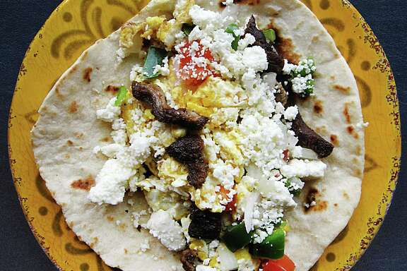 Julio Cesar Chavez taco (scrambled eggs, beef fajita, pico de gallo and queso fresco) on a handmade flour tortilla from El Taconazo.