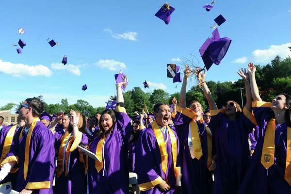 Senior class president Andrew Putterman, center, screams as his classmates throw their caps in the air following the Westhill High School graduation on the football field behind the school in Stamford, Conn. on Tuesday, June 20, 2017.
