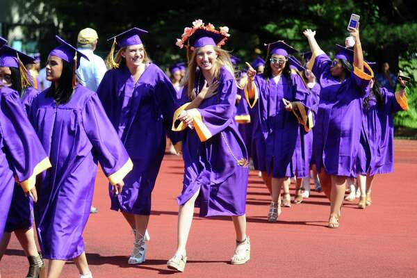 Elizabeth Ruffels, center, smiles as she spots her family while walking towards the football field for the Westhill High School graduation in Stamford, Conn. on Tuesday, June 20, 2017.