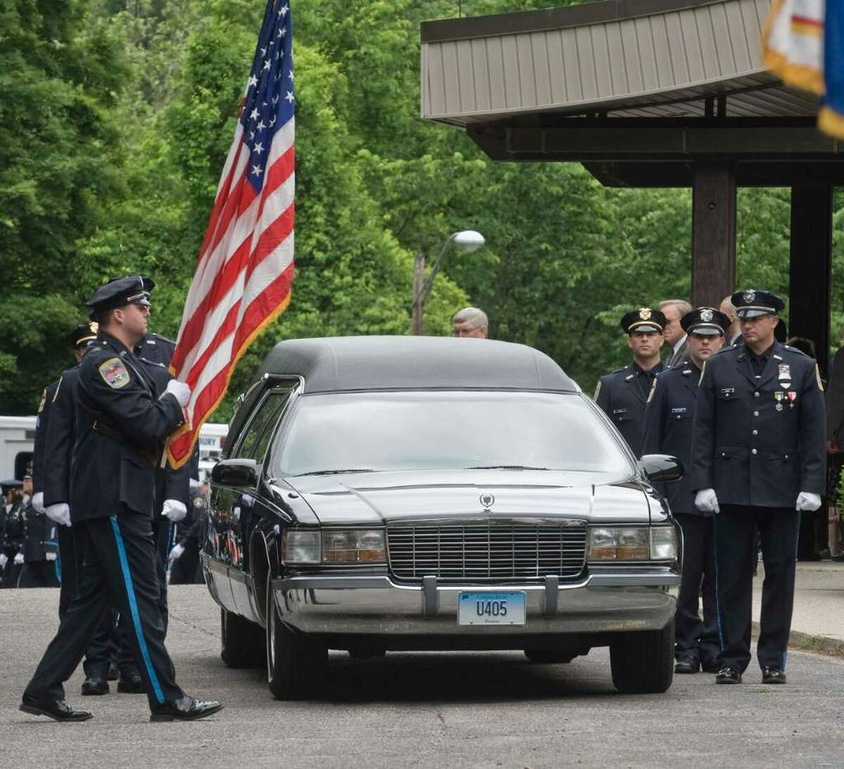 Danbury police stand alongside the hearse of Danbury Police Officer Donald Hassiak at St. Francis Xavier Roman Catholic Church in New Milford. Wednesday, June 9, 2010