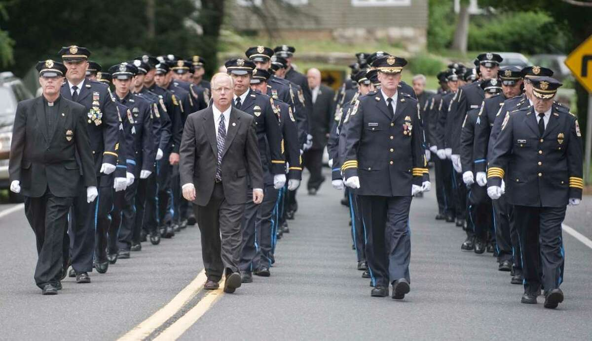 The Danbury Police Department is led by Mayor Mark Boughton at the close of the funeral for Danbury Police Officer Donald Hassiak at St. Francis Xavier Roman Catholic Church in New Milford. Wednesday, June 9, 2010