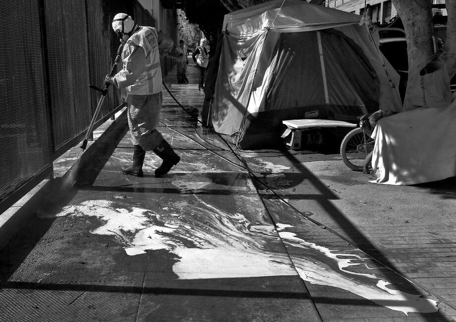 Marc Jacoban, a member of the S.F. Public Works homeless cleanup crew, power washes the sidewalk next to a row of tents. Photo: Leah Millis, The Chronicle