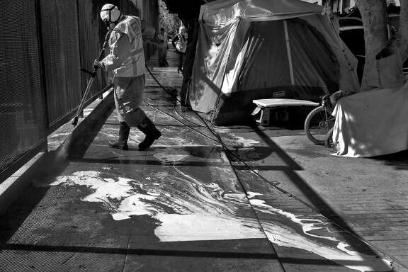 Marc Jacoban, a member of the San Francisco Public Works Homeless Outreach Team (HOT) power washes the sidewalk next to a row of tents June 2, 2017 in San Francisco, Calif. The crew sometimes shows up to camps solely to clean them, not to clear them out.
