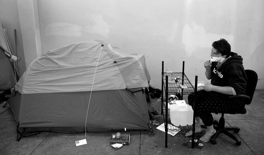 Brian Borland shaves in front of his tent in a homeless encampment at Utah and 15th streets in San Francisco. Borland has been living on the streets since he arrived from Washington state about a year ago. Photo: Paul Chinn, The Chronicle