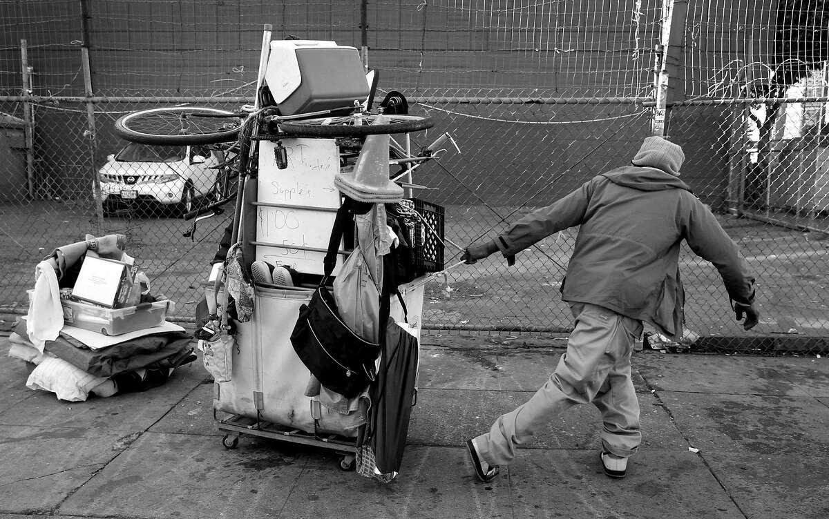 Markael Rayvon hauls his belongings after the homeless encampment he was living in was taken down at 14th and Mission streets before a Public Works Hot Spots crew can clean up and disinfect the sidewalk in San Francisco, Calif. on Tuesday, March 14, 2017.