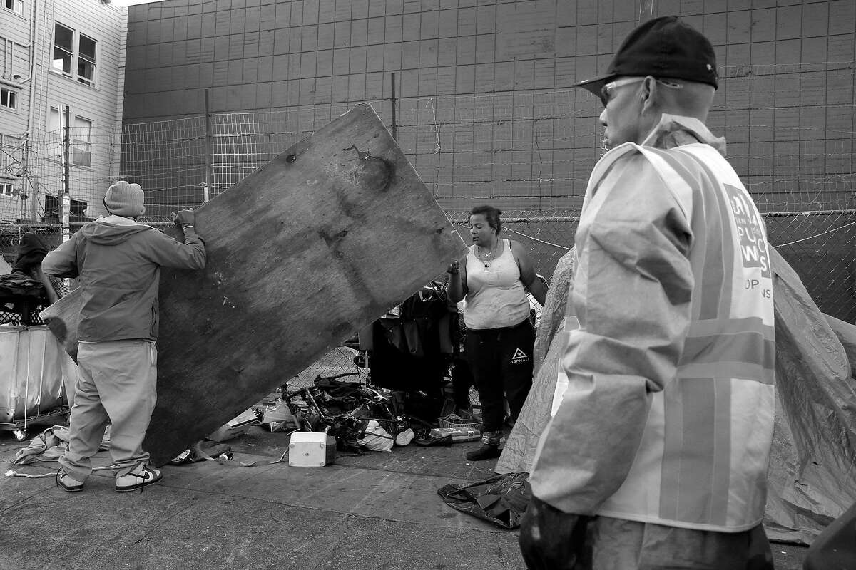A Public Works crew waits for residents of a homeless encampment to clear out before cleaning and disinfecting the sidewalk at 14th and Mission streets in San Francisco, Calif. on Tuesday, March 14, 2017.