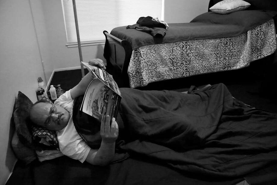 Luis Castellanos reads as he lies on the floor in his bedroom next to the new bed in his apartment in the Richmond District. Castellanos says he still hasn't gotten used to having his own bed, so on the floor he lays down the old bed clothes from his time camping in Golden Gate Park so he can get to sleep. Photo: Lea Suzuki, The Chronicle