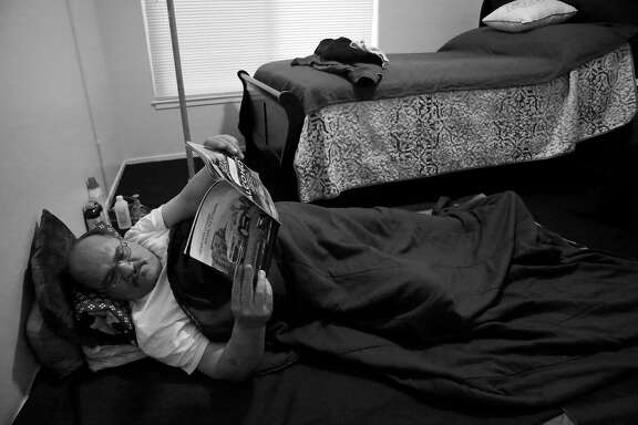 Luis Castellano reads as he lays on the floor in his bedroom next to the new bed in his apartment on Monday, May 22, 2017 in San Francisco, Calif.  Castellano says he is still lays down the bed clothes he used while camping in Golden Gate Park to sleep on his floor in his new apartment.