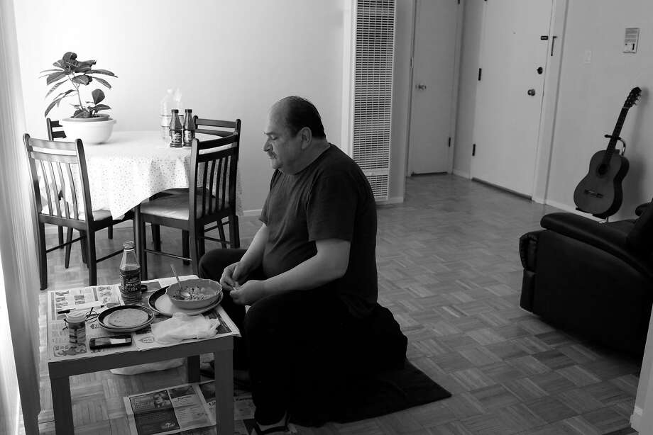 Luis Castellanos sits down on crate at a small table next to his dining table to eat his home made soup for lunch at his home on Monday, June 12, 2017 in San Francisco, Calif.  Castellano says he feels more comfortable sitting at the smaller table in his home as he gets used to his new home. Photo: Lea Suzuki, The Chronicle