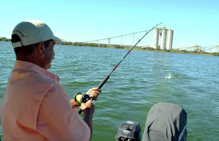 A hook up within sight of the coal-fired CPS Energy plant gives Leo Saenz some good blue catfish action during a trip with Guide Manny Martinez at Calaveras Lake.