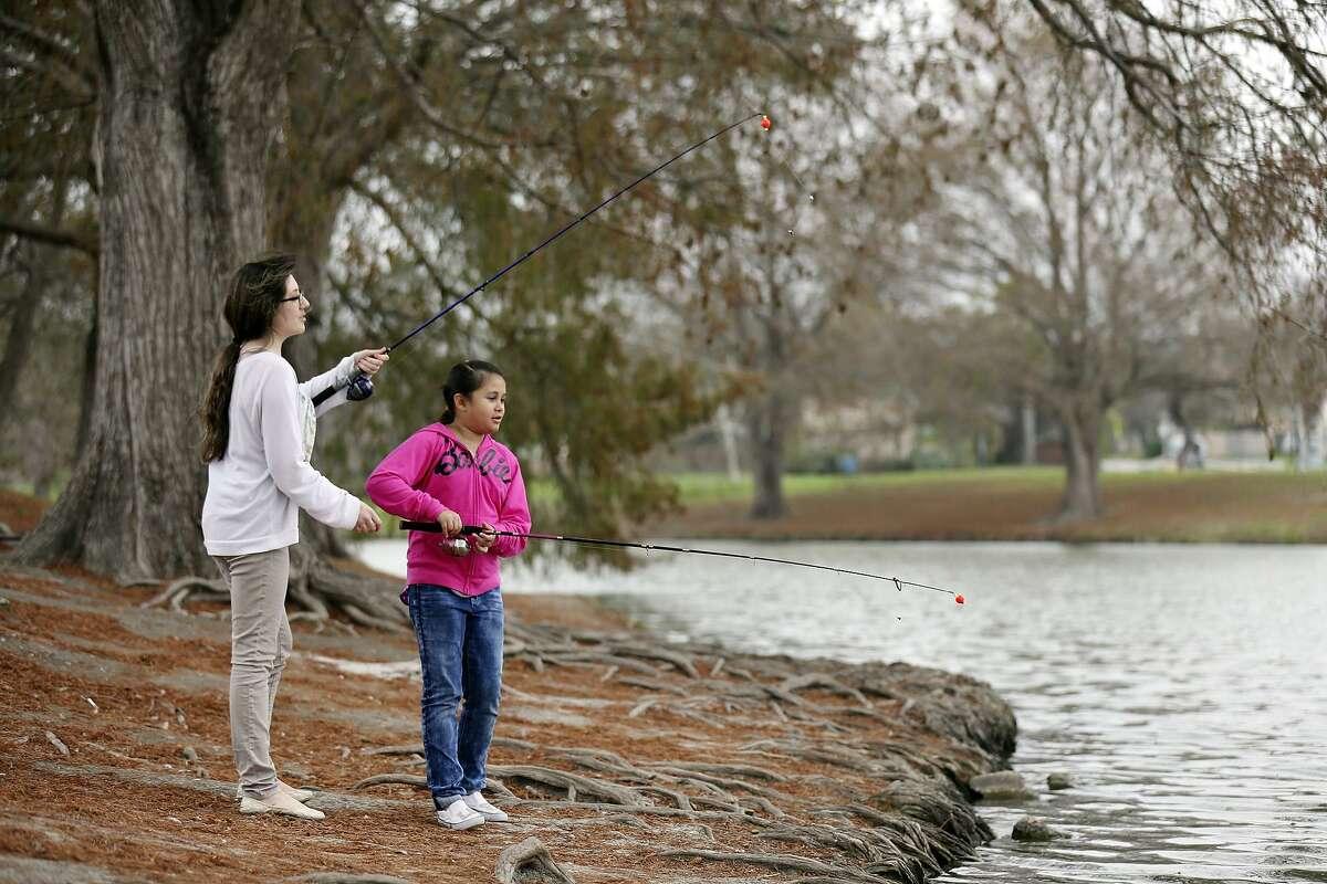 Sisters Suriya Mason (let), 24, and Savanna Mason, 8, fish at Woodlawn Lake.
