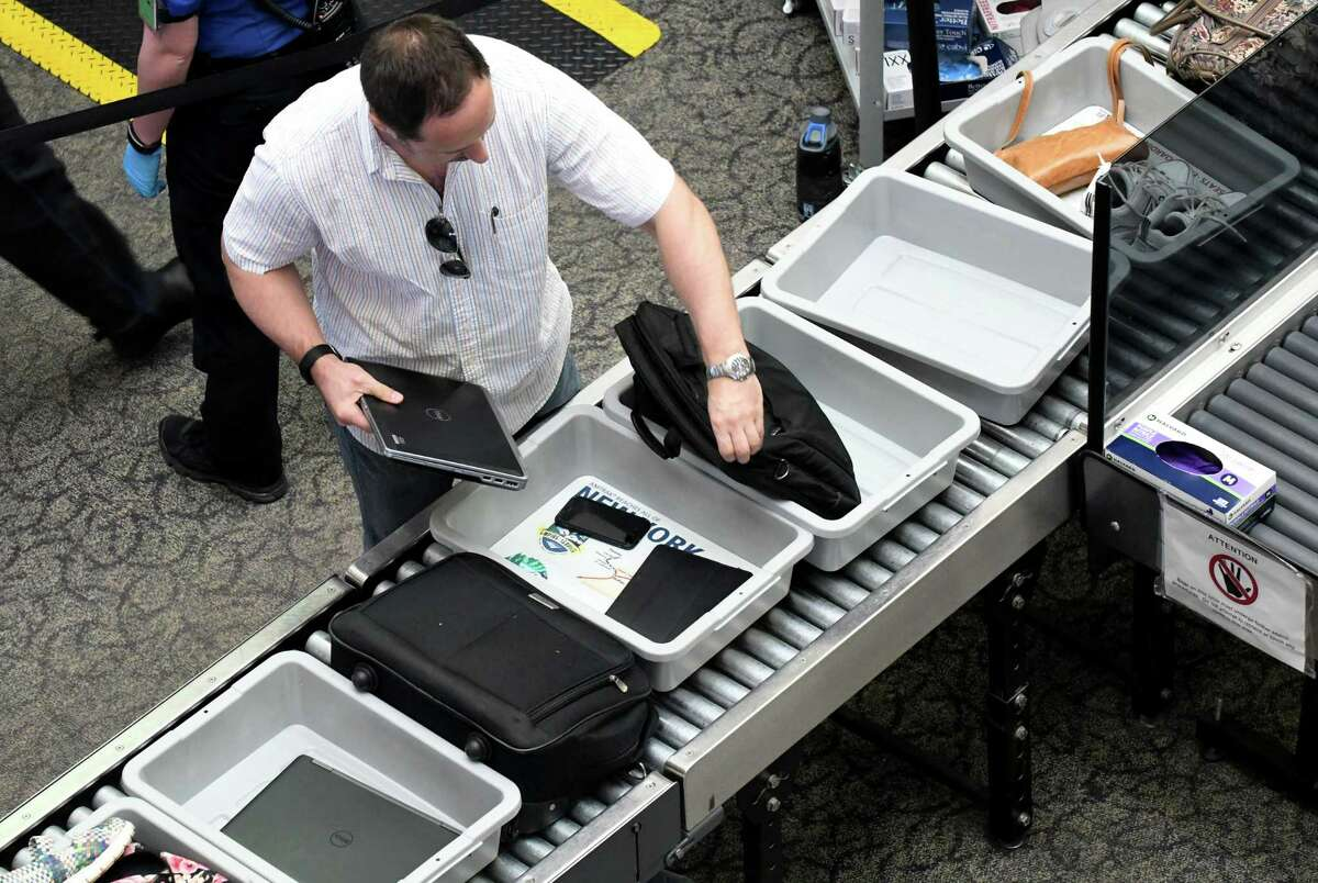 An air passenger removes his laptop computer from its bag for security screening at Albany International Airport on Tuesday, June 20, 2017, in Colonie, N.Y. Other electronics larger than a cellphone also will have to be removed from baggage and placed in bins, under new procedures announced Thursday. (Will Waldron/Times Union)