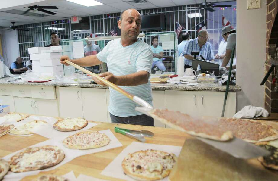 As business picks up, Haidar Assi, owner of Cedar Bakery, takes manakish, a Lebanese pizza, out of the pizza oven to feed hungry late-night customers at 1:30 am. The restaurant is open for 24 hours on Friday, Saturday and Sunday during Ramadan. Photo: Elizabeth Conley, Staff / © 2017 Houston Chronicle