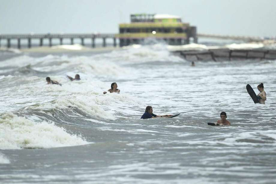 People enjoy the waves on boogie boards Tuesday at Galveston in advance of Tropical Storm Cindy's arrival. Photo: Elizabeth Conley /Houston Chronicle / © 2017 Houston Chronicle