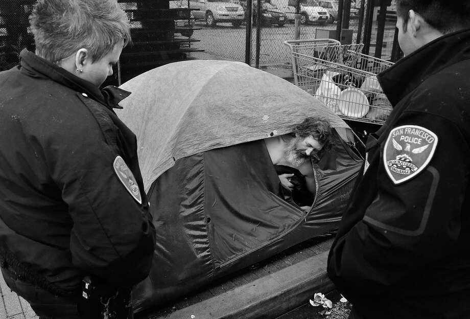 Officers Y. Strickfaden (left) and Louie Benavidez, members of the Police Department's Homeless Outreach Unit, visit an encampment along Folsom Street and talk with Army vet John Hunter to offer him help through various city programs. Photo: Michael Macor, The Chronicle