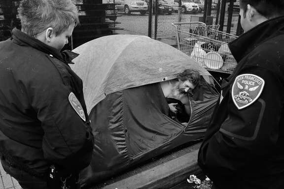 Officers Y. Strickfaden (left) and Louie Benavidez, members of the Police Department's Homeless Outreach Unit, visit an encampment along Folsom Street and talk with Army vet John Hunter to offer him help through various city programs.