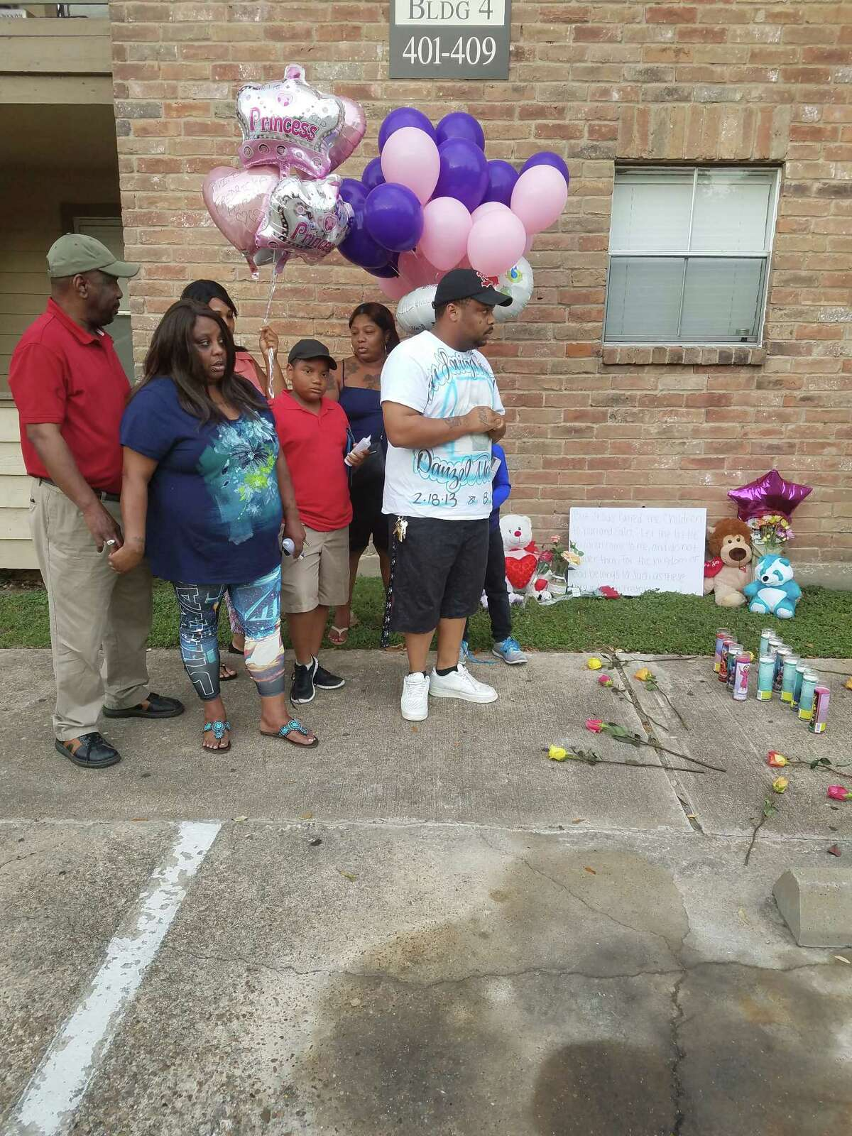 Randy Sample and other family members gather at Timberwalk apartments for a vigil held Tuesday in honor of their dead 4-year-old relative Fredricka Allen.