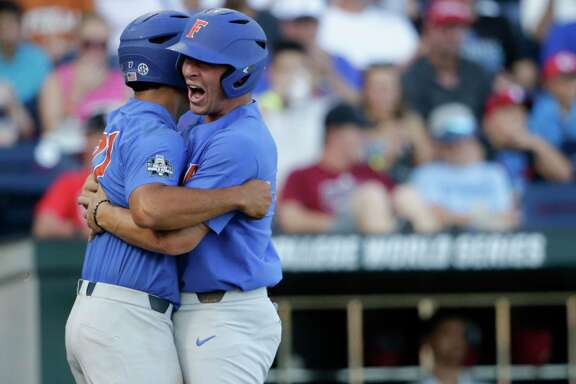 Florida's Nelson Maldon-ado, left, and Jonathan India embrace after scor-ing on a three-run home run by Deacon Liput.